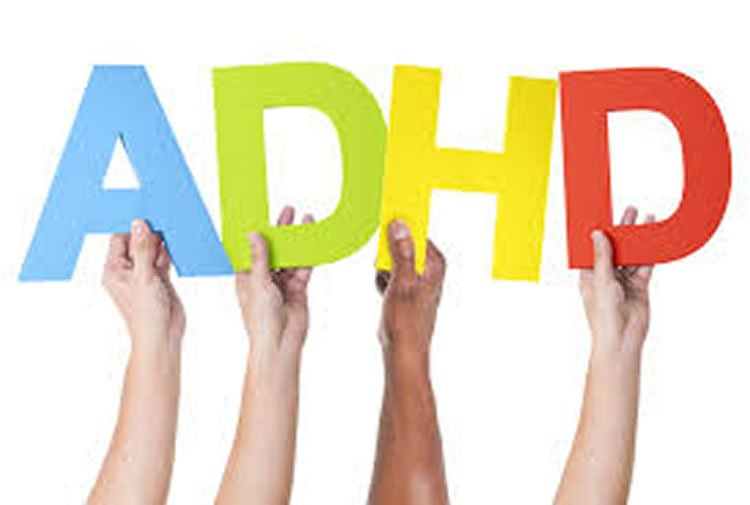 Image shows people holding up the letters ADHD.