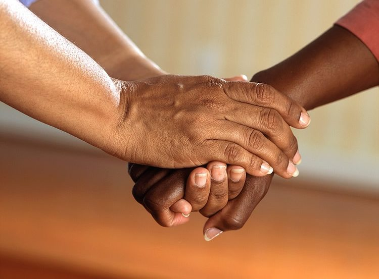 Image shows people holding hands.