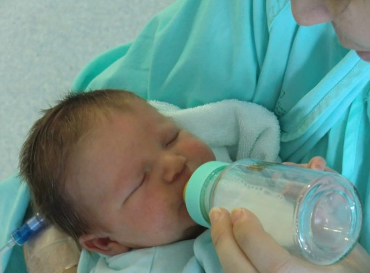 Image shows a mom feeding her baby with a bottle of milk.