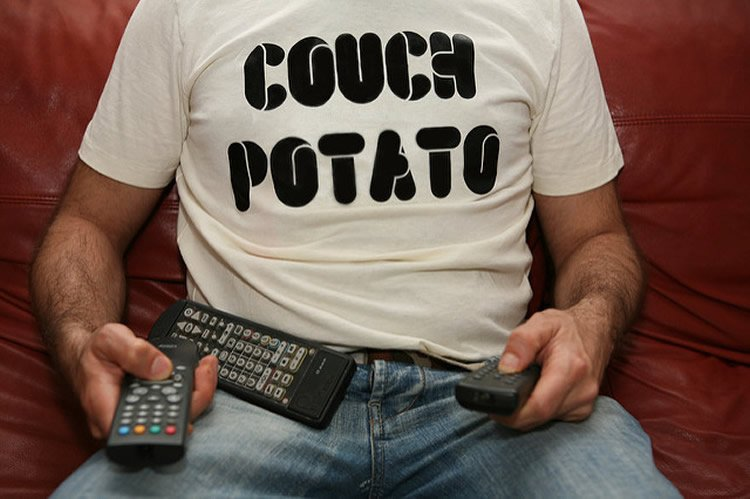 A man sitting on a couch wearing a couch potato t-shirt.