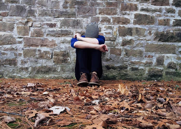 Image shows a depressed looking person.