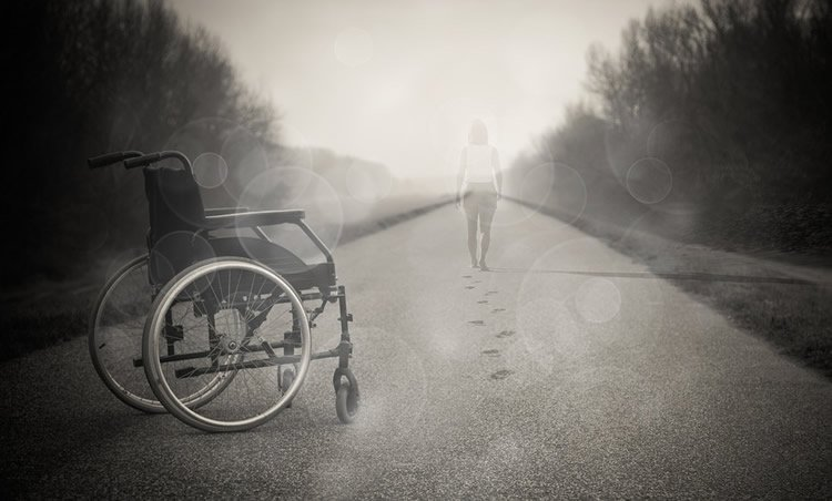 Image shows a woman walking away from a wheelchair.