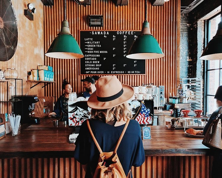 Image shows a woman at a coffee shop counter.