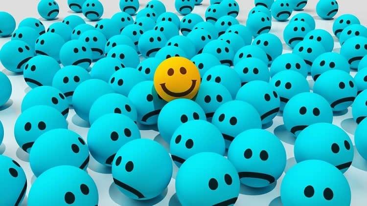 Image shows a smiley yellow ball among sad blue balls.