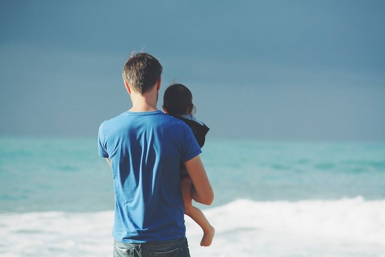 Image shows a dad and toddler looking at the sea.