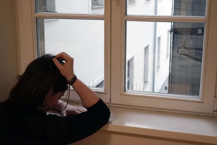 Image shows a depressed woman looking out a window.