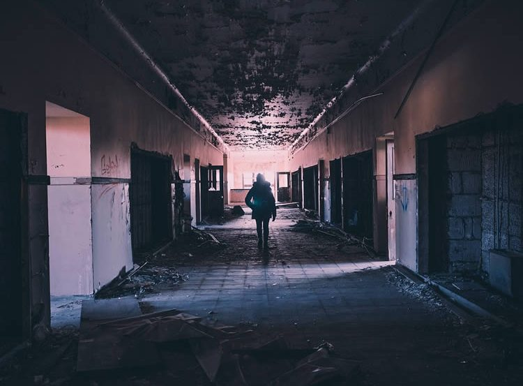 Image shows a person walking alone through a corridor.