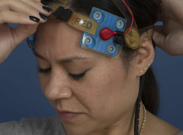 Image shows a woman using the tDCS equipment.