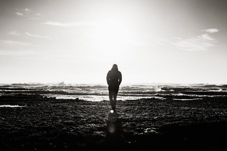Image shows a man walking with his back to the camera.