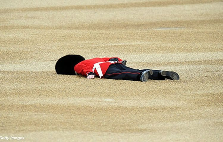 Image shows a Queen's Guard laying on the floor after fainting.