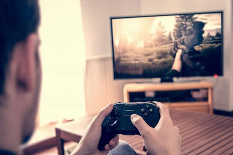 Image shows a man playing a video game.