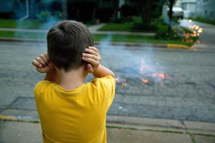 Image shows a boy holding his ears while watching fireworks.