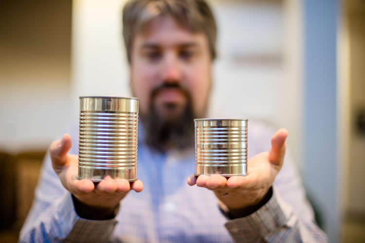 Image shows a big tin can and a smaller tin can.