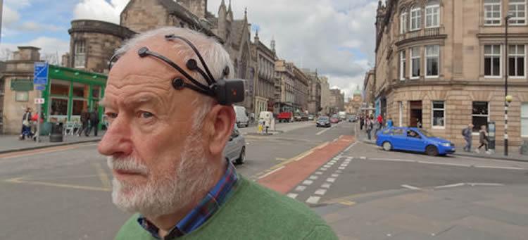 Image shows a man in an EEG cap.