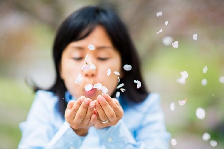 Image shows a woman blowing petals.
