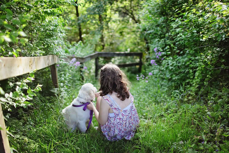 Image shows a girl and a dog.