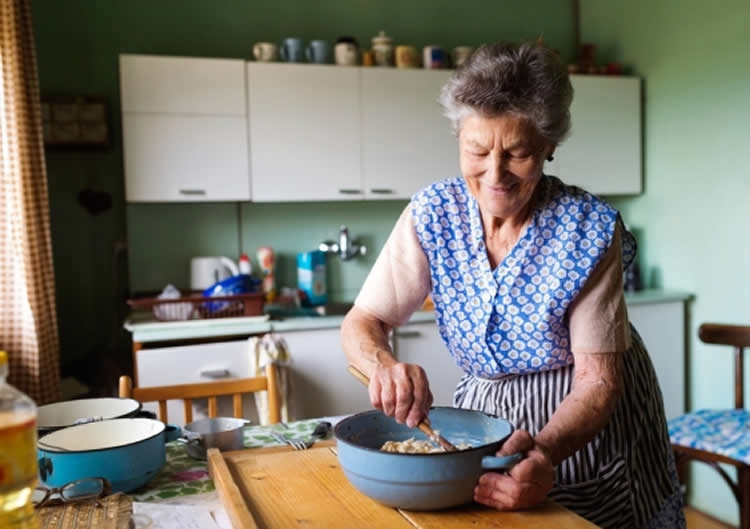 Image shows an old lady baking.