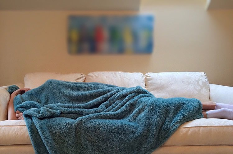 Image shows a person sleeping on a couch.
