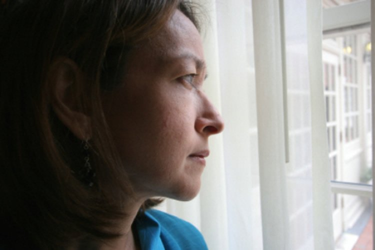 Image shows a woman looking out a window.