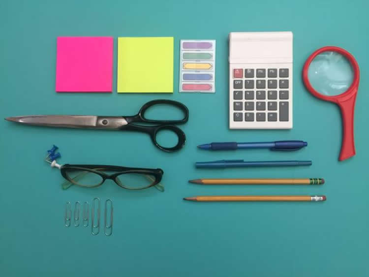 Image shows desk items such as pens, pins and clips, all in straight line.
