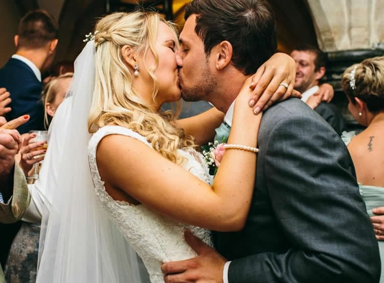 Image shows a married couple kissing.