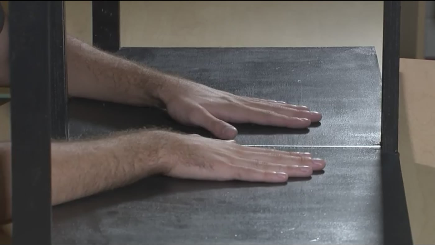 Image shows a person with his hand infront of a mirror.