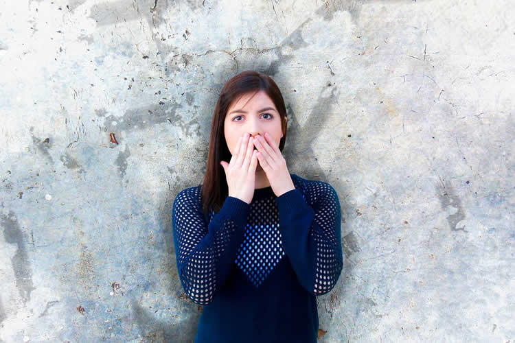 Image shows a woman covering her mouth.
