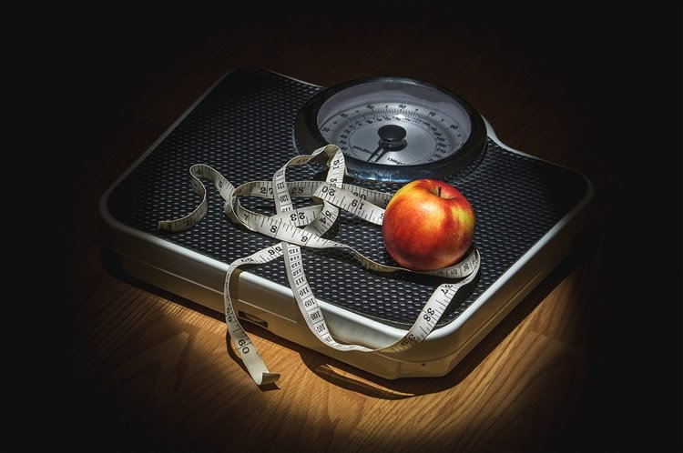 Image shows scales, an apple and tape measure.