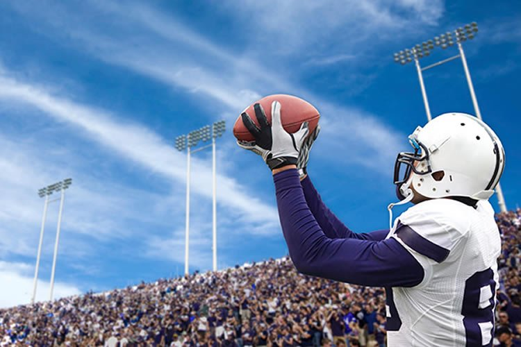 Image shows a football player catching the ball.