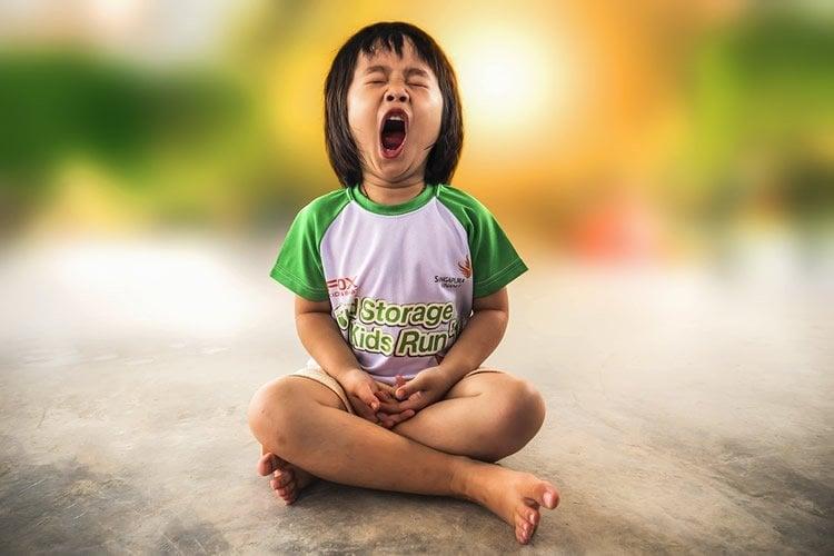 Image shows a child yawning.
