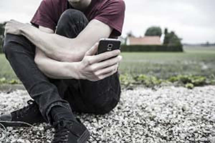 Image shows a teen boy looking at a cell phone.