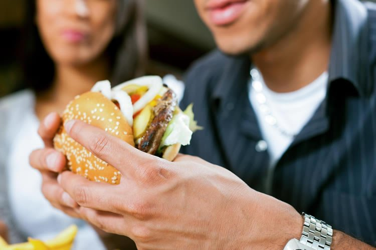 Image shows a person eating a burger.