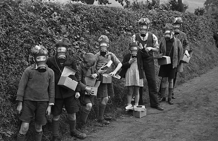Image shows children in gas masks.