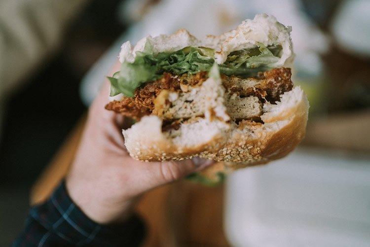 Image shows a man eating a burger.