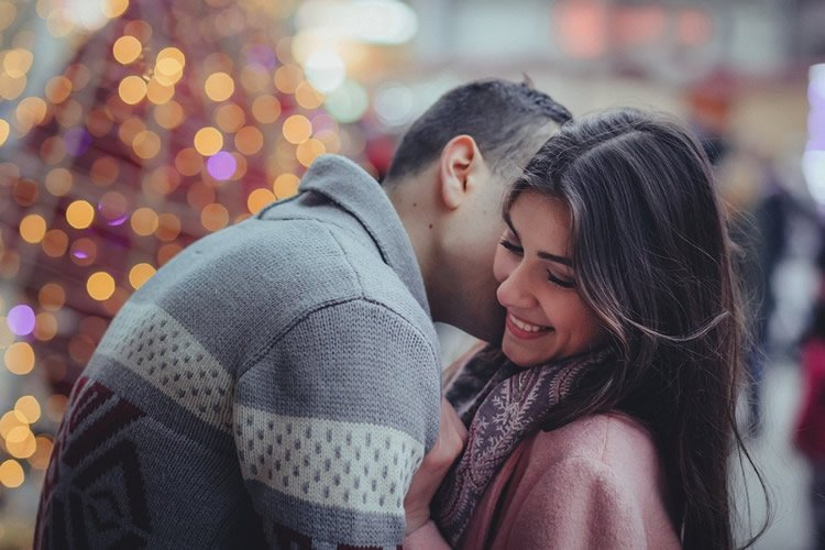 Image shows a couple kissing by a christmas tree.