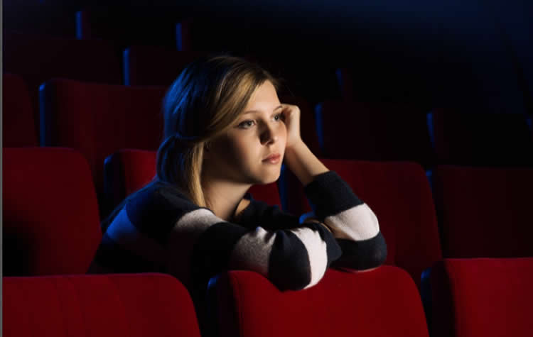 Image shows a sad lookinh woman in a movie theatre.