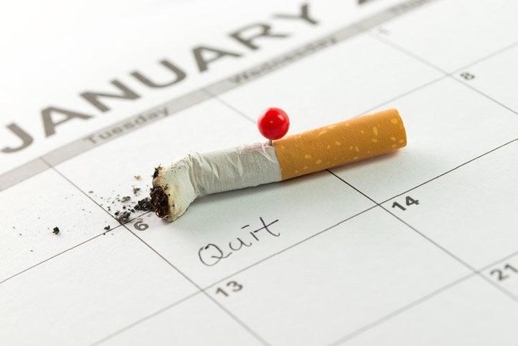 Image shows a stubbed out cigarette on a calendar.