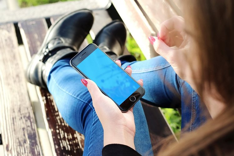 Image shows a girl using a smartphone.