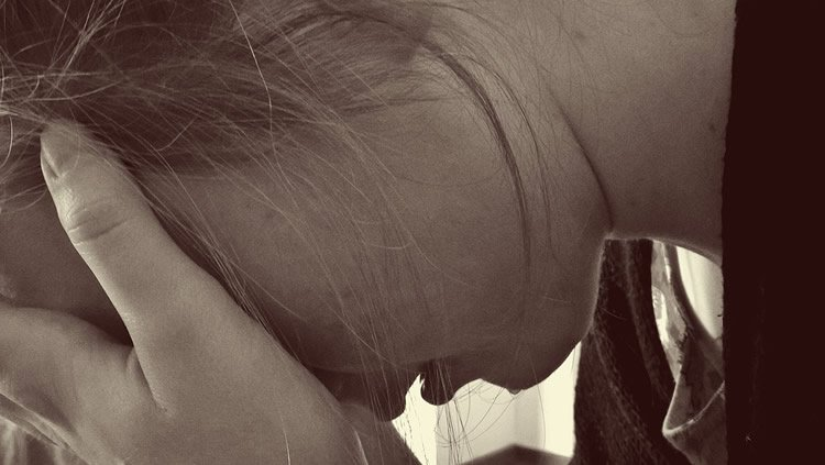 Image shows a girl holding her head in her hands.