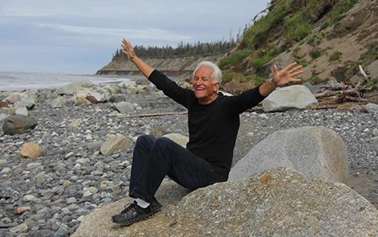an older man sitting on a beach