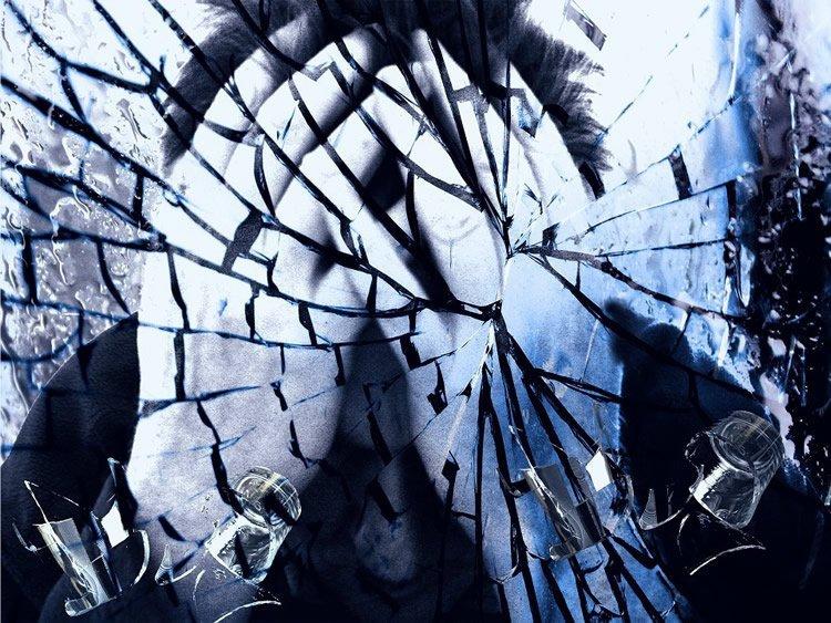 a man behind broken glass