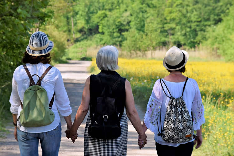 an older lady and two younger ladies walking in a park