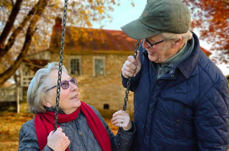 an older couple sitting on a swing