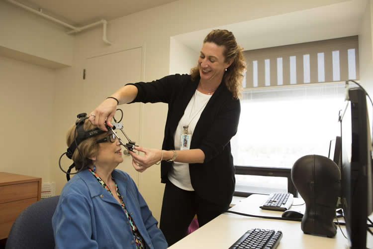 researcher fitting eye tracking equipment onto an older lady