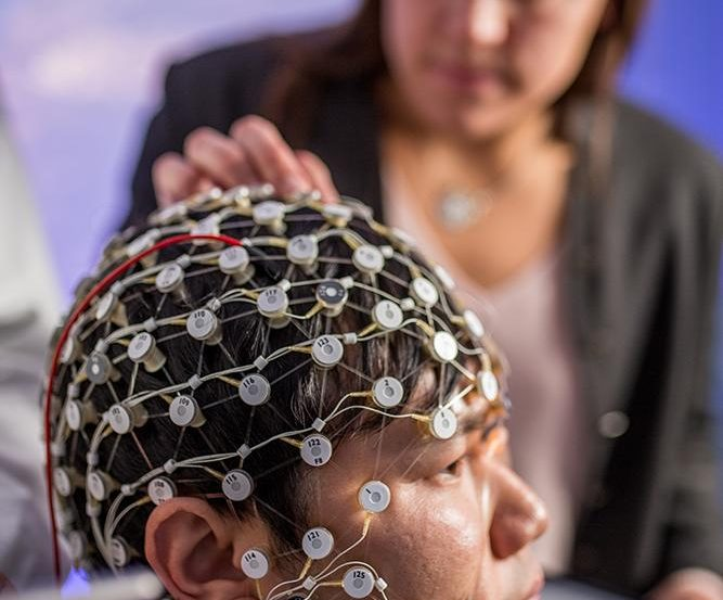 A person's head is covered in electrode netting as another person touches an electrode.