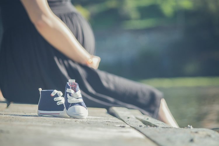 a pregnant woman and a pair of baby shoes are shown here