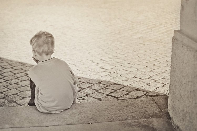 a young boy sitting on a step