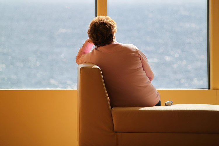 an older woman looking out of a window