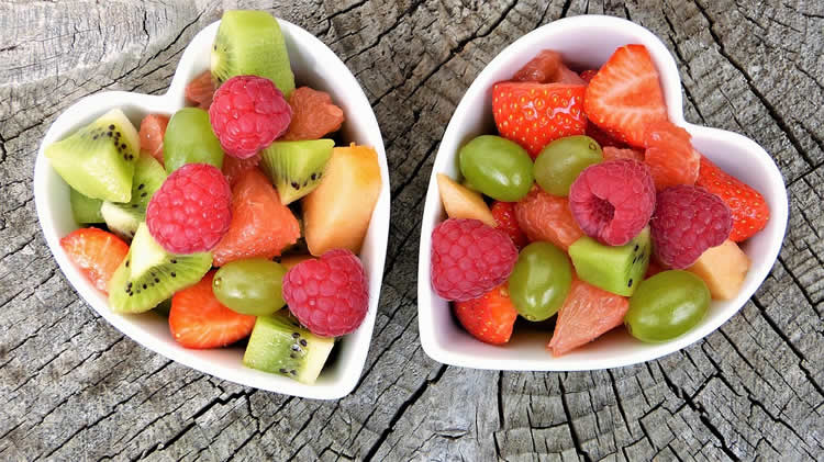 Two bowls shaped like hearts are filled with fruits.