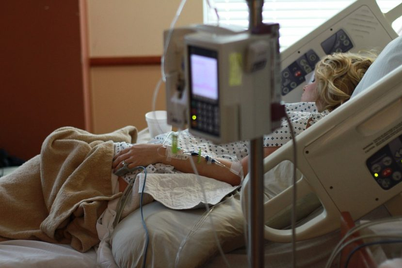 A woman is shown in a hospital bed.